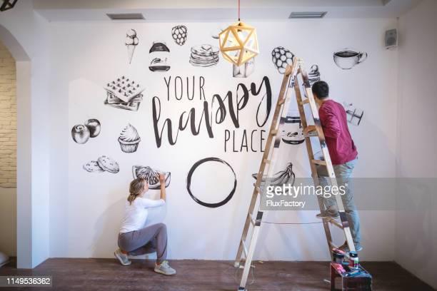 motivated couple doing some needed home improvement - murale foto e immagini stock