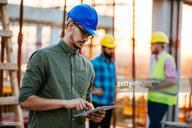 motivated engineer working with colleagues and using internet - satisfaction stock pictures, royalty-free photos & images
