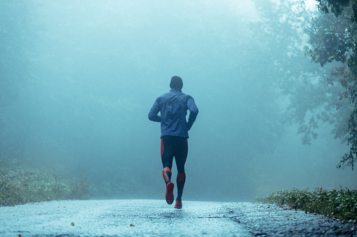 Motivated young man running in the rain. 943894690