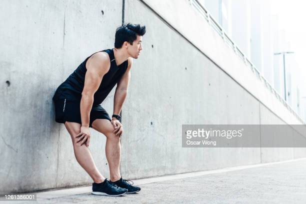 motivated young man taking a break after running in the city - men stock pictures, royalty-free photos & images