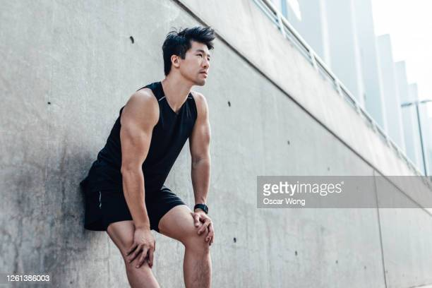 motivated young man taking a break after running in the city - males stock pictures, royalty-free photos & images