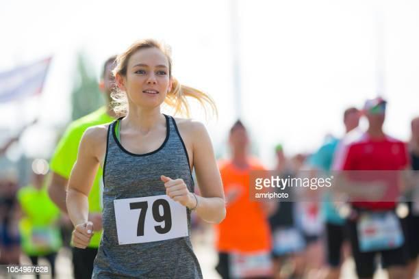 motivato giovane donna correre maratona - maratona foto e immagini stock