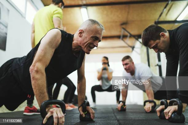 motivation for healthy living - cross training for all ages with private trainer. - circuit training stock photos and pictures