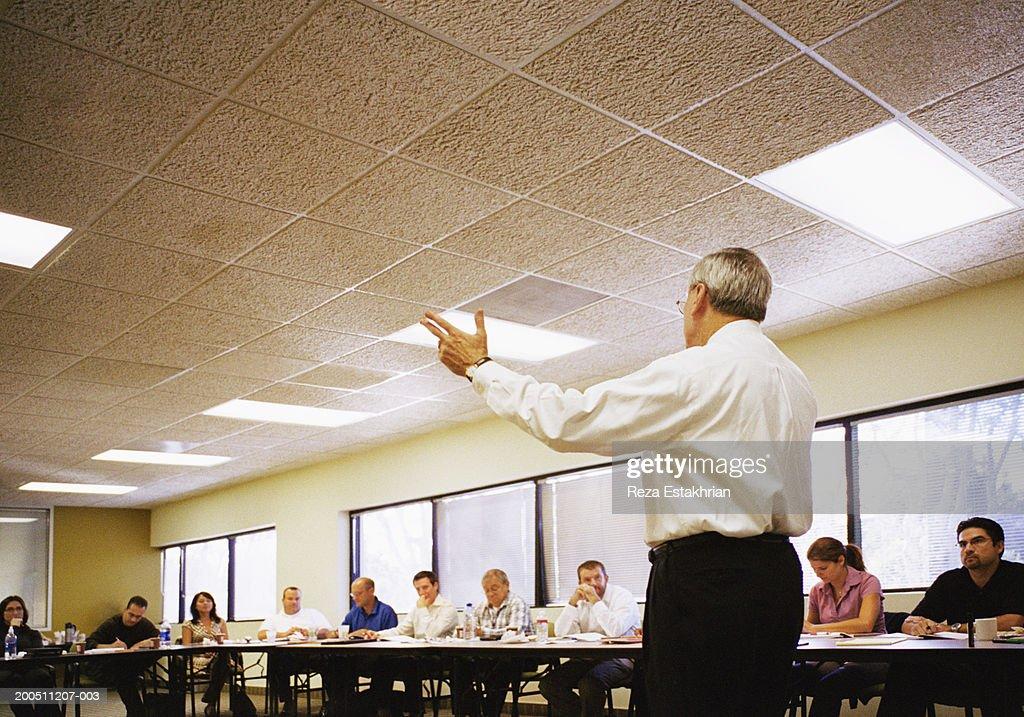 Motivational speaker addressing business people : Stock Photo