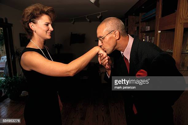 Motivational speaker and author Joe Kita kisses a woman's hand in his home