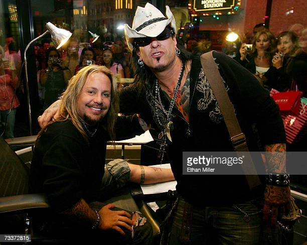 Motley Crue singer Vince Neil and bassist Nikki Sixx pose as Neil gets the first tattoo at his Vince Neil Ink tattoo parlor during the shop's grand...