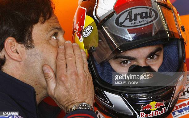 Moto GP driver spanish Dani Pedrosa listens his manager Alberto Puig in the box before the first free practice session of the Grand Prix of Portugal...