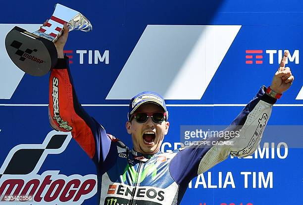 Moto GP Spanish rider Jorge Lorenzo celebrates on the podium after winning the Moto Grand Prix ahead of Spain's Marc Marquez and Italian Andrea...