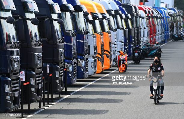 Moto GP team member wears a face mask as she rides her motorcycle through the paddock during the second training session ahead of the Moto GP Czech...