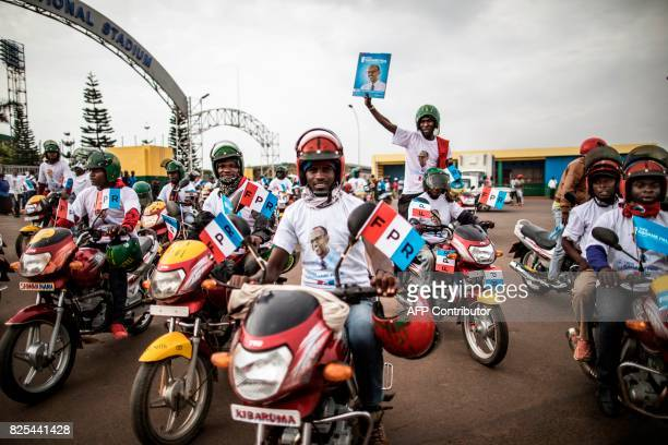 Moto taxi driver hold flags of the governing Rwanda Patriotic Front's at the start of a parade in Kigali on August 2 2017 Incumbent Rwandan President...