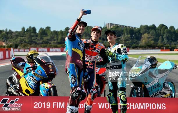 Moto2 world champion EG 0,0 Marc VDS's Spanish rider Alex Marquez takes a selfie picture with MotoGP world champion Repsol Honda Team's Spanish rider...