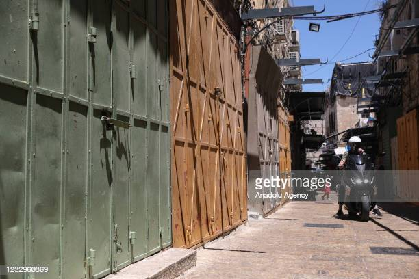 Motobiker passes by closed shops as shopkeepers go on a general strike to protest against Israeli attacks over Gaza and East Jerusalem on May 18,...