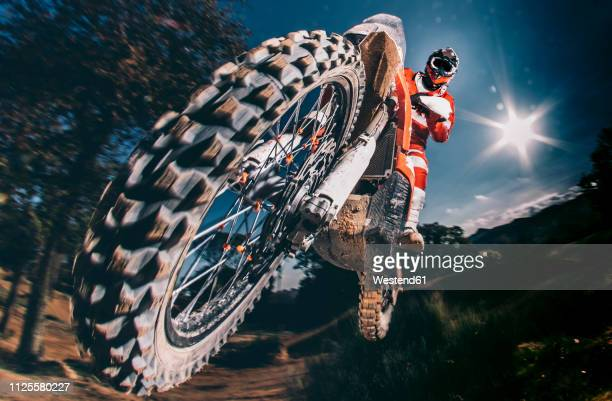 motocross biker jumping - scrambling stock pictures, royalty-free photos & images
