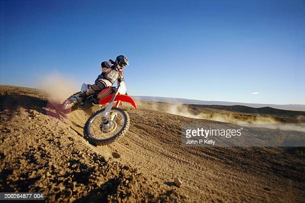 Motocross driver on dirt road, side view