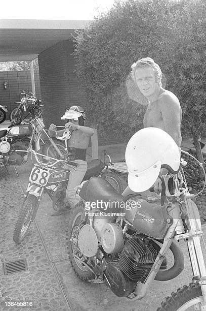Portrait of celebrity actor Steve McQueen with his son Chad McQueen and his bike collection in his garage Palm Springs CA CREDIT Heinz Kluetmeier