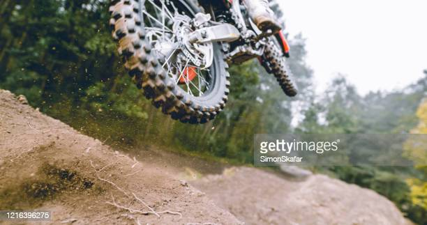 motocross racer in mid-air above dirt track in forest - 20 29 years stock pictures, royalty-free photos & images