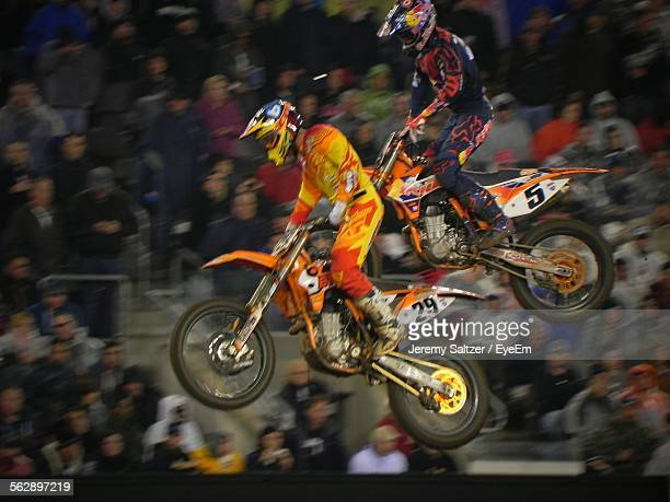 motocross racers in mid-air at event - scrambling stock photos and pictures