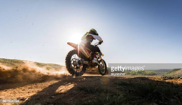 motocross rider driving fast while racing on dirt track. - motorcycle racing stock pictures, royalty-free photos & images