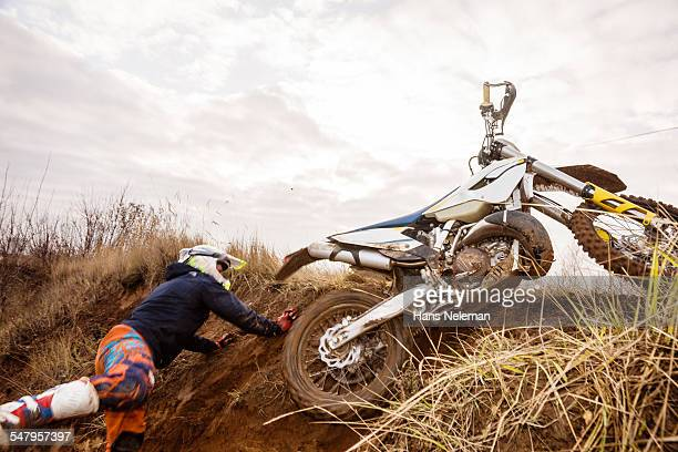 Motocross rider falls off motorcycle during race