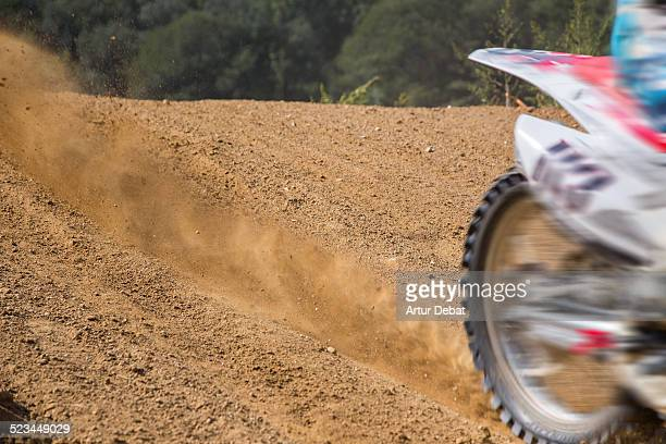 Motocross rider in ground track with dusty trail