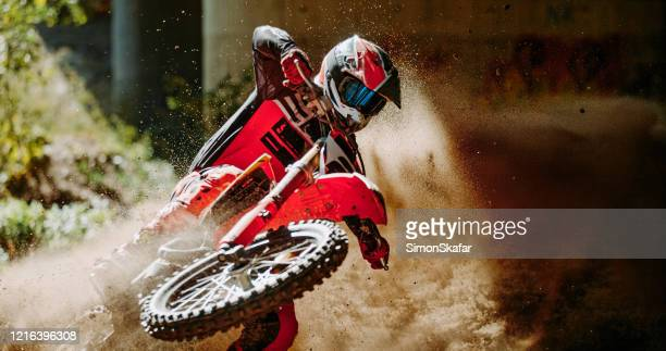 motocross rider in red sportswear raced on dirt track in forest - 20 29 years stock pictures, royalty-free photos & images