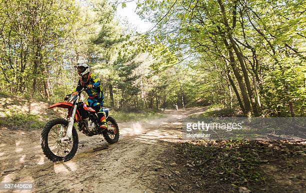 Motocross rider racing on a dirt track in the forest.