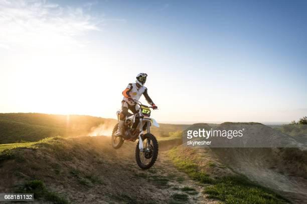 Motocross rider racing over dirt hills at sunset.
