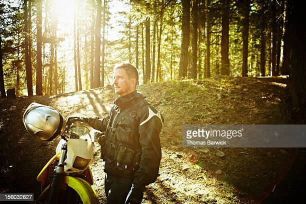 Motocross rider standing next to bike in forest