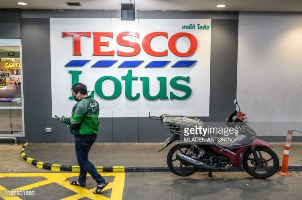 A motocurrier enters a TescoLotus supermarket in Bangkok on December 11 2019 Supermarket chain Tesco Britain's biggest retailer said that it was...