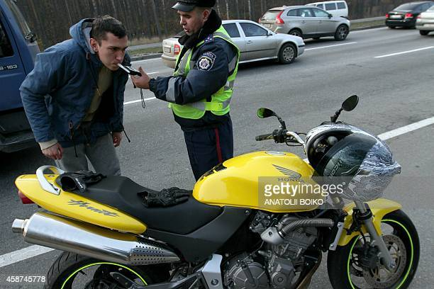 A motocycle rider blows into an alcohol breathalyzer as Police officers stop cars to control the presence of alcohol in the blood of drivers as part...