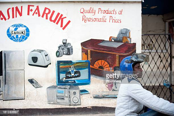 A motocycle taxi rider waits for customers in front of a sign advertising luxury goods for sale in central Kigali Rwanda on Wednesday Sept 18 2013...