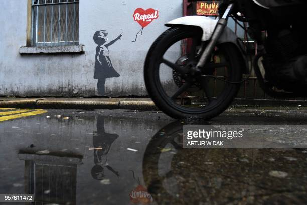 A motocyclist passes by a prochoice mural based on a work by Banksy urging a yes vote in the referendum to repeal the eighth amendment of the Irish...