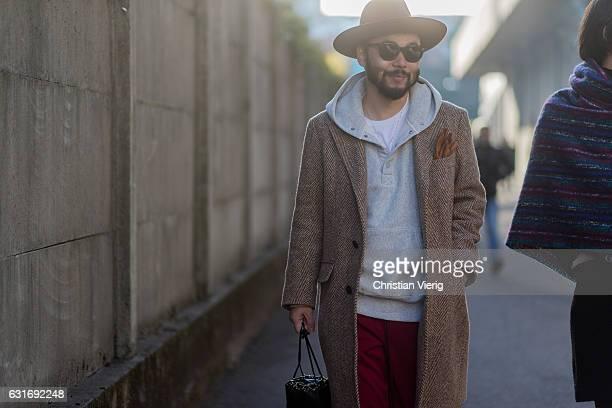 Motofumi Kogi 'Poggy' wearing a coat hat hoody is seen at Diesel during Milan Men's Fashion Week Fall/Winter 2017/18 on January 14 2017 in Milan Italy