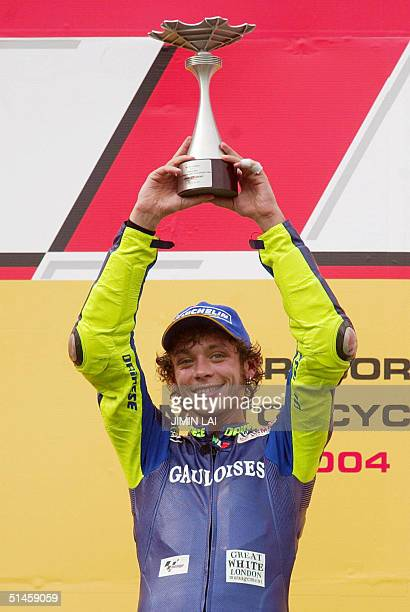 MotoGP champion Valentino Rossi of Italy raises his trophy after winning the Malaysian MotoGP in Sepang 10 October 2004 Rossi won the Malaysian...