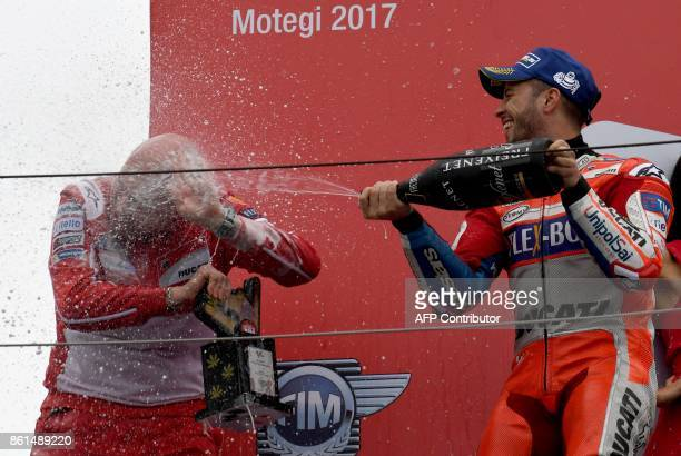 TOPSHOT MotoGP class winner Ducati rider Andrea Dovizioso of Italy sprays champagne to his team officer Gabriele Conti on the podium during the...