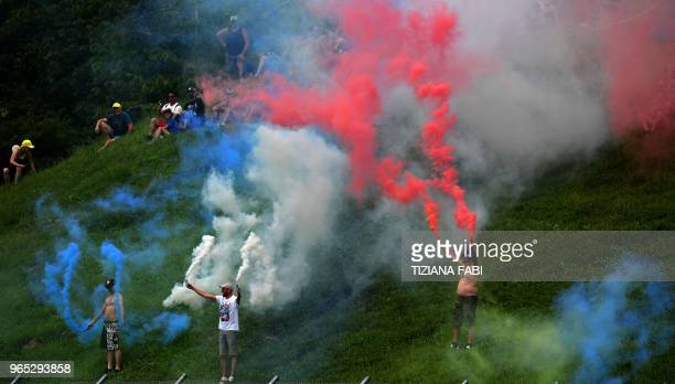 MotoGP fans hold smoke canisters during a free practice session ahead of the Italian MotoGP Grand Prix at the Mugello racetrack in Scarperia e San...