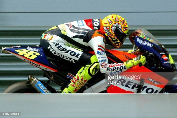 MotoGP World Champion Italian rider Valentino Rossi ducks inside the front visor of his Repsol Honda as he speeds past the grandstand on the main...
