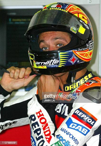 MotoGP World Champion Italian rider Valentino Rossi of Repsol Honda puts on his helmet at the pits of the Sepang International Circuit during the...