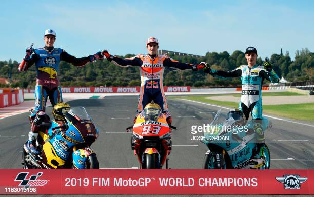MotoGP world champion Repsol Honda Team's Spanish rider Marc Marquez poses with Moto2 world champion EG 0,0 Marc VDS's Spanish rider Alex Marquez and...