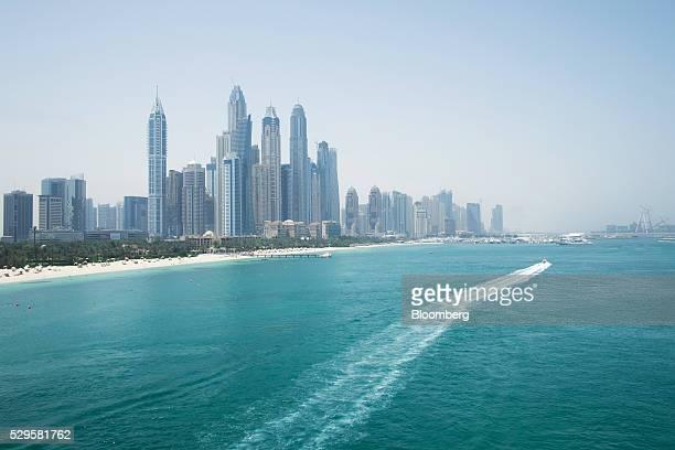 A motor boat heads along the coastline towards the Dubai Marina district seen from the Palm Monorail public tram in Dubai United Arab Emirates on...