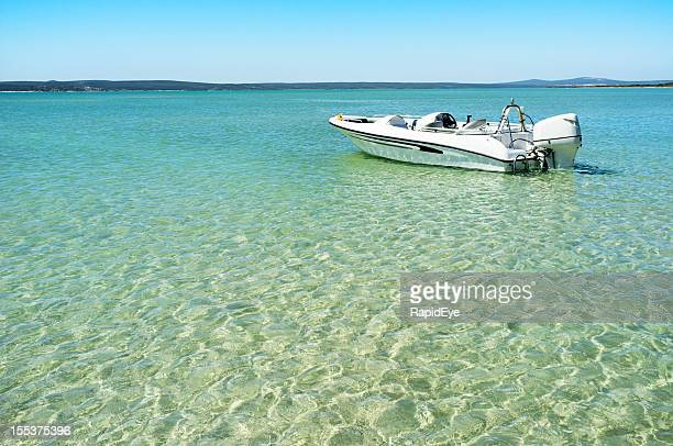 Motor boat moored in turquoise lagoon waters on summer day