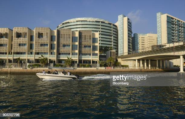 A motor boat passes new residential apartment blocks in the Al Muneera gated enclave developed by Carillion Plc and AlFuttaim Group on the Al Raha...