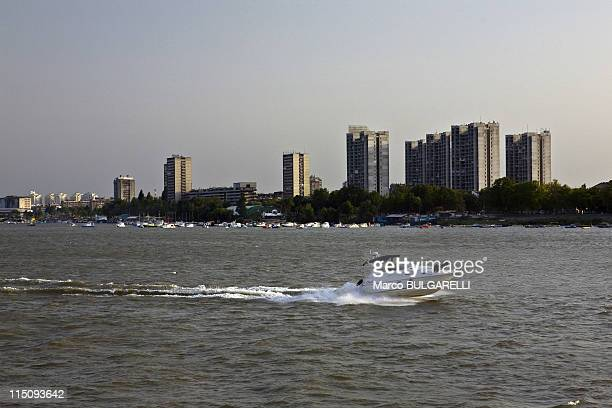 Motor boat travels on the Danube with apartment blocks of Novi Beograd in the background on August 15 2008 in Belgrade Serbia