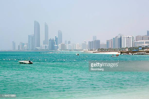Motor boats sit at their moorings on a waterway backdropped by the city skyline in Abu Dhabi United Arab Emirates on Monday Aug 12 2013 As Dubai...