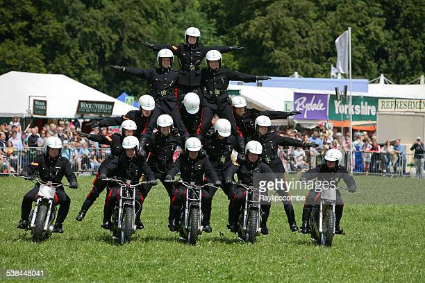 motor cycle display team, perform a tricky pyramid move - human pyramid stock photos and pictures