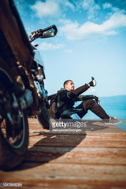 motor driver is making a selfie on wooden deck by the lake - biker jacket stock pictures, royalty-free photos & images