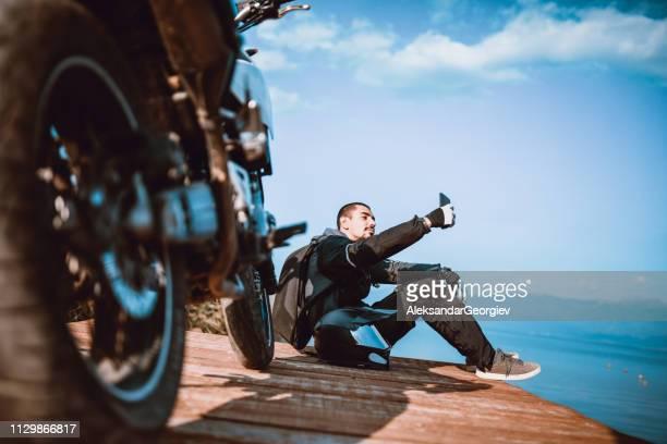 モータ ドライバー、湖のほとりに木製デッキ、selfie をしています。 - オートバイ競技 ストックフォトと画像