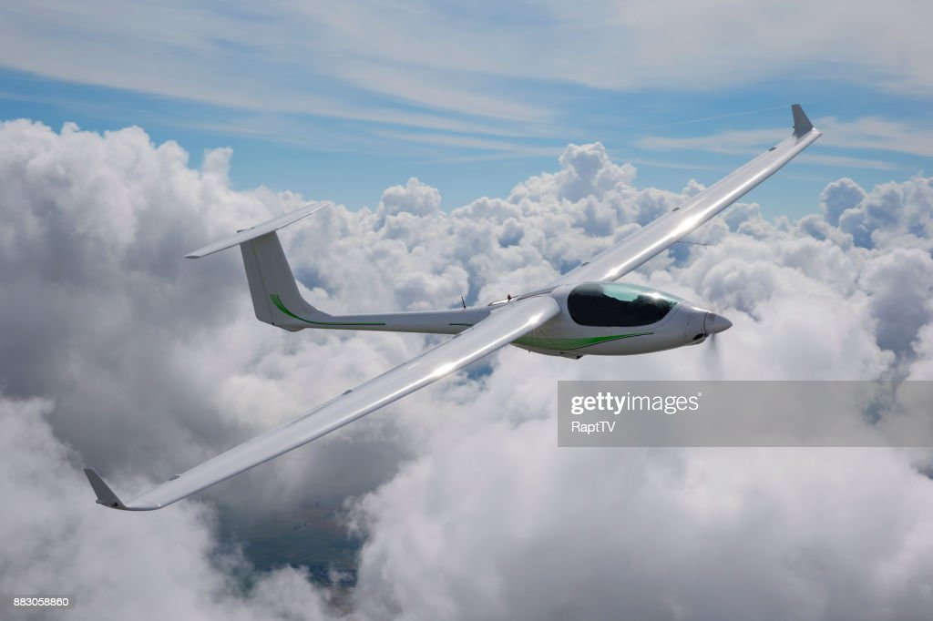 A Motor Glider Using it's Engine to gain Altitude over the Clouds. : Stock Photo