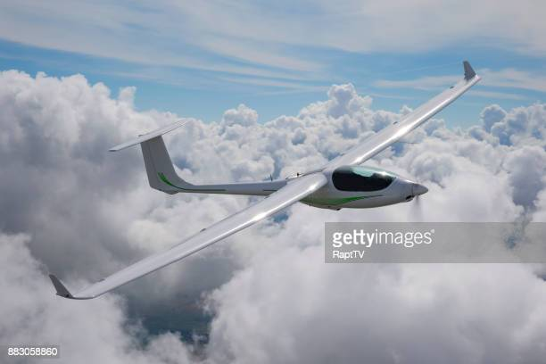a motor glider using it's engine to gain altitude over the clouds. - glider - fotografias e filmes do acervo