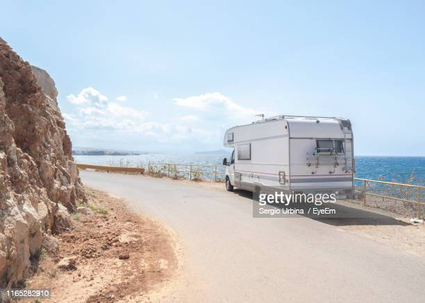 motor home on road by sea against sky during sunny day - camper stockfoto's en -beelden